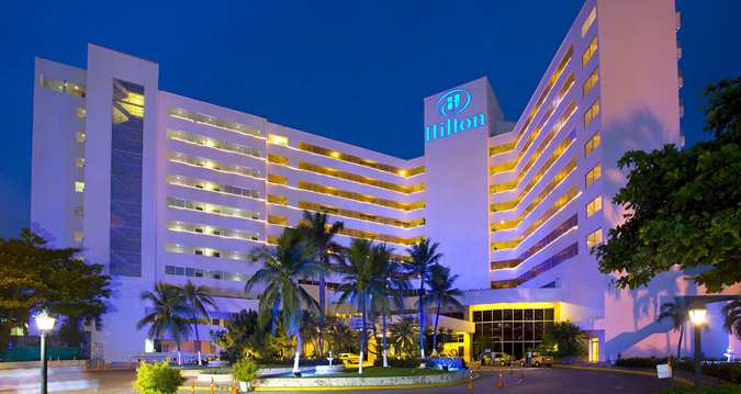 """The Hilton Cartagena, with its Main & Executive Towers and its Convention Center is known as """"The Best Place Anytime"""". Thanks to its multiple facilities and services, has the great attribute to be able to host simultaneous events and conventions, giving also to its visitors the opportunity to enjoy relax and comfort.  Surrounded by water its seems to be a ship sailing into the deep ocean."""